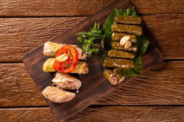 Arabic food. appetizing cabbage rolls and rice and mint wrapped in grape vine leaves on wood background.