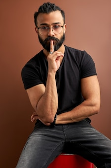 Arabic guy keep silence, isolated on brown studio background, handsome guy hold finger near mouth, look at camera