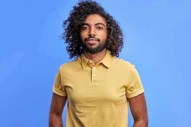 Arabic guy posing confidently looking at camera, young bearded male with dark skin in studio on blue space