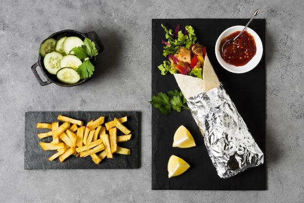 Сэндвич с арабским кебабом, завернутый в алюминиевую фольгу, вид сверху
