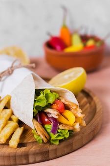 Сэндвич с арабским кебабом, завернутый в белую бумагу, высокий вид