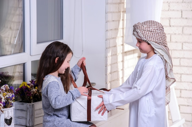 Arabic kids unpacking the gift box.