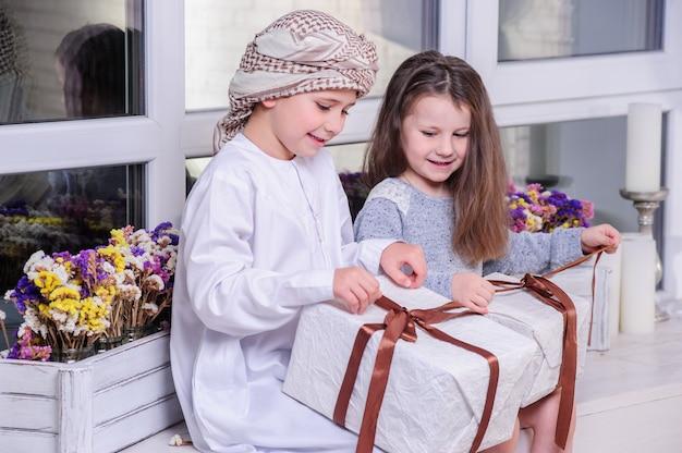 선물을 풀고 있는 아랍 아이들.