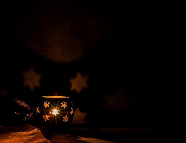 이슬람 휴일을 위해 밤에 촛불과 대추야자 열매가 있는 아랍 랜턴. 이슬람 성월 라마단. 이드 마무리하고 새해 복 많이 받으세요. 어두운 배경에 공간을 복사합니다.