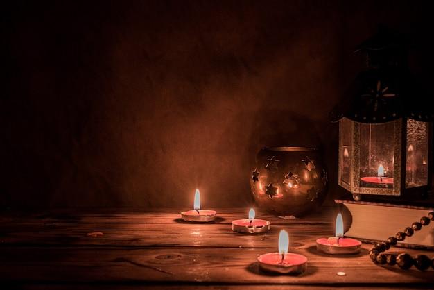 이슬람 휴일을 위해 밤에 촛불을 든 아랍 랜턴. 이슬람 성월 라마단. 이드 마무리하고 새해 복 많이 받으세요. 어두운 배경에 공간을 복사합니다.