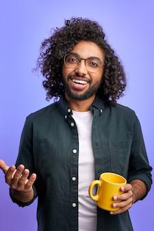 アラビア語の男性を見て、お茶を飲み、話し、笑顔。紫色の壁に隔離