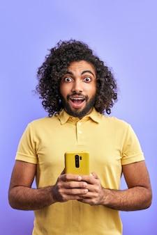 スマートフォンでメッセージを読んで驚いたアラビア人男性、巻き毛の男性スタンドがメッセージに感情的に反応し、口を開けてカメラを見る