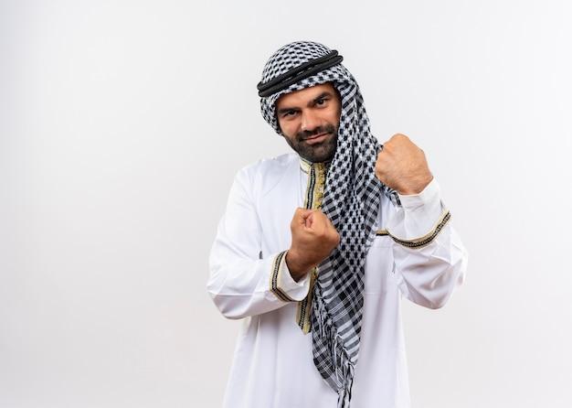 Арабский мужчина в традиционной одежде, сжимая кулаки, счастлив и позитивно улыбается, стоя над белой стеной