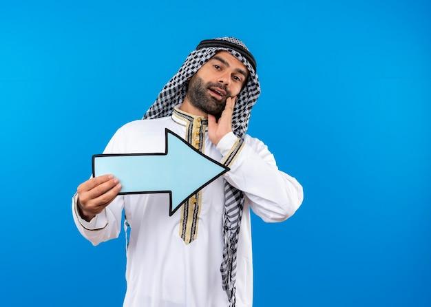 青い壁の上に立って右の笑顔を指す大きな青い矢印を保持している伝統的な服を着たアラビア人男性