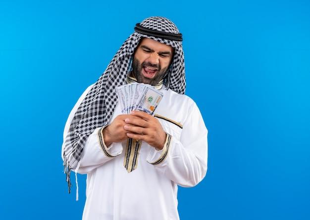 Арабский мужчина в традиционной одежде держит деньги, весело улыбаясь, стоя у синей стены