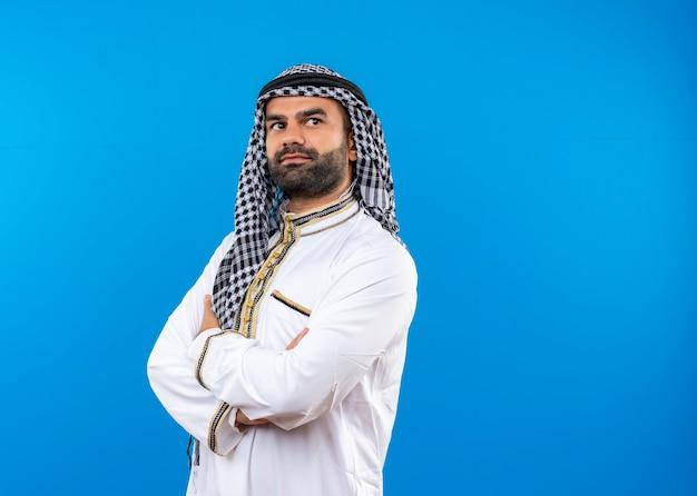 Арабский мужчина в традиционной одежде, уверенно глядя в сторону со скрещенными руками на груди, стоит у синей стены