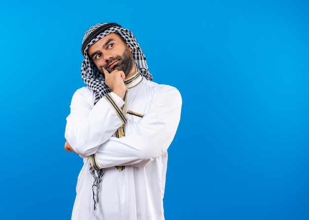 Арабский мужчина в традиционной одежде смотрит в сторону, положив руку на подбородок, думает, стоя над синей стеной