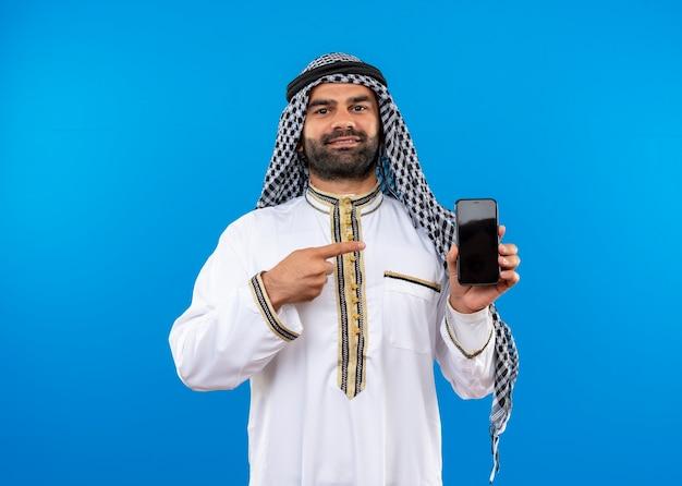 Арабский мужчина в традиционной одежде показывает смартфон, указывая пальцем на него, уверенно улыбаясь, стоя над синей стеной