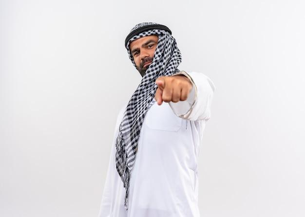 Арабский мужчина в традиционной одежде, уверенно улыбаясь, указывая указательным пальцем на белую стену