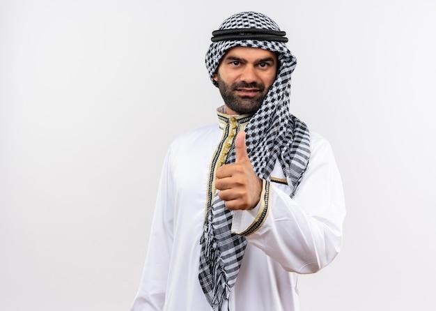 Арабский мужчина в традиционной одежде улыбается, показывает палец вверх, стоя над белой стеной