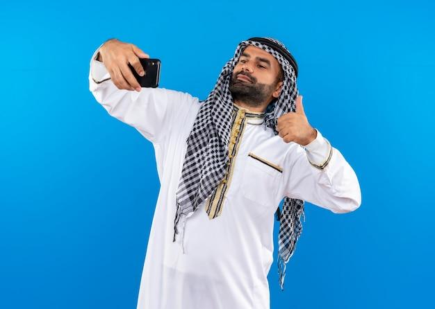 Арабский мужчина в традиционной одежде, делающий селфи с помощью смартфона, показывает палец вверх, стоя над синей стеной