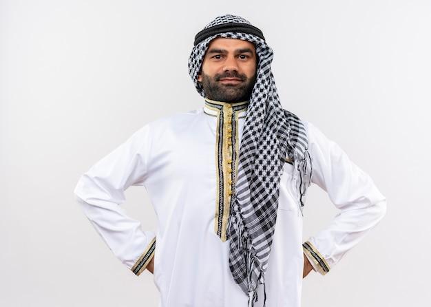 Арабский мужчина в традиционной одежде с уверенной улыбкой на лице стоит над белой стеной