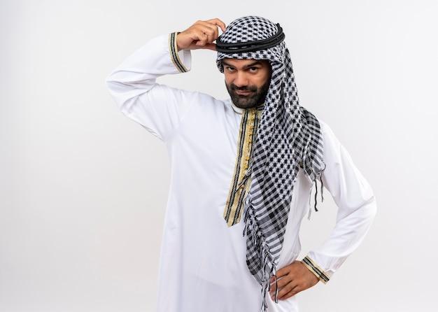 Арабский мужчина в традиционной одежде с септическим выражением лица почесывает голову пальцем, стоящим над белой стеной