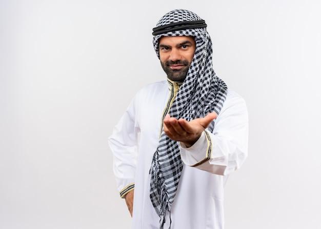 Арабский мужчина в традиционной одежде с улыбкой на лице, предлагающий приветствие рукой, стоя над белой стеной