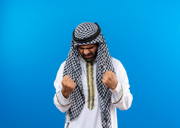 Arabic man in traditional wear clenching fist with angry face standing over blue wall