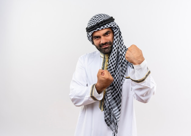 Arabic man in traditional wear clenching fists happy and positive smiling standing over white wall