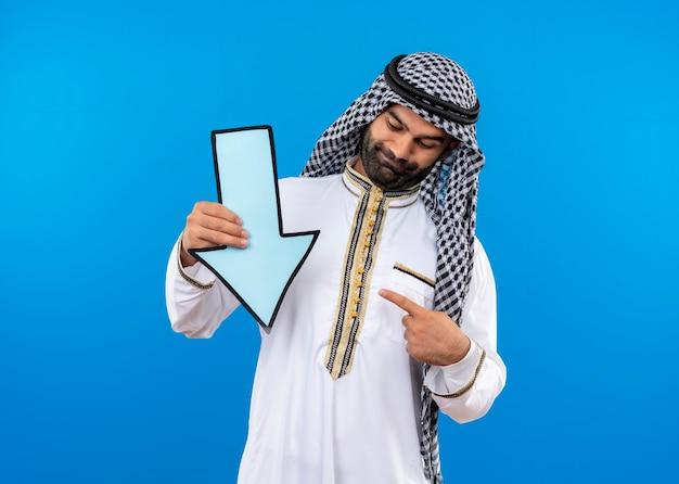 Uomo arabo in abbigliamento tradizionale che tiene grande freccia blu rivolta verso il basso che punta con il dito ad esso sorridente in piedi sopra la parete blu
