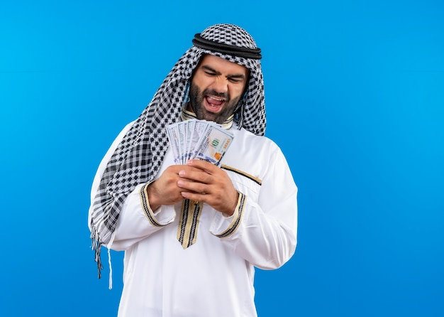 Arabic man in traditional wear holding cash smiling cheerfully standing over blue wall