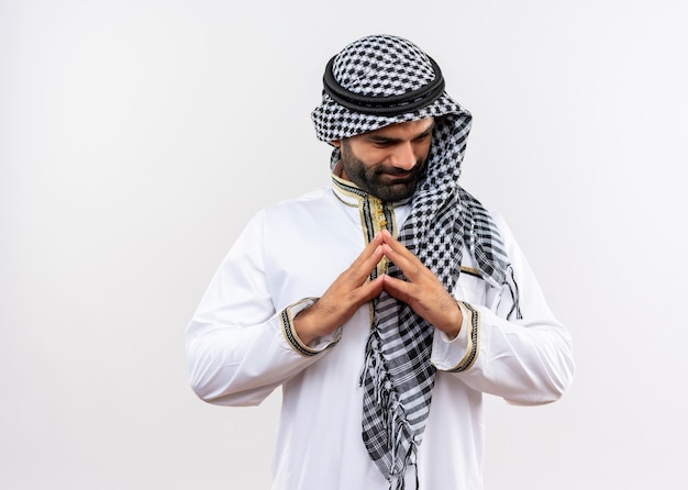 Arabic man in traditional wear holding palms together looking aside with smile on face standing over white wall