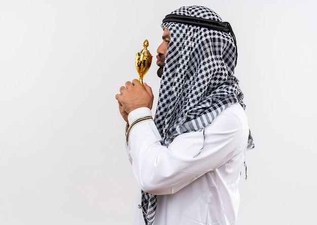 Arabic man in traditional wear kissing his trophy standing sideways over white wall