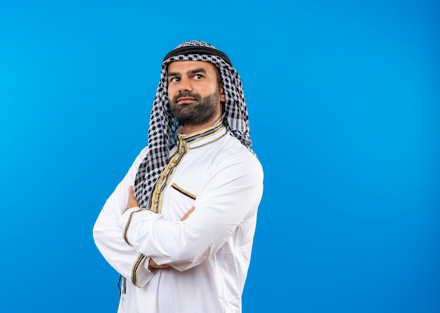 Arabic man in traditional wear looking aside with confident expression with crossed hands on chest standing over blue wall