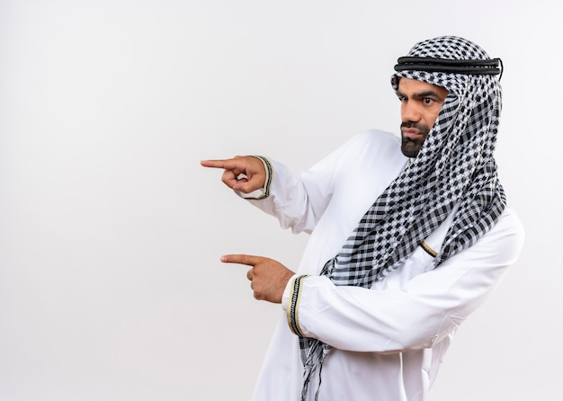 Arabic man in traditional wear looking aside with serious face pointing with fingers to the side standing over white wall