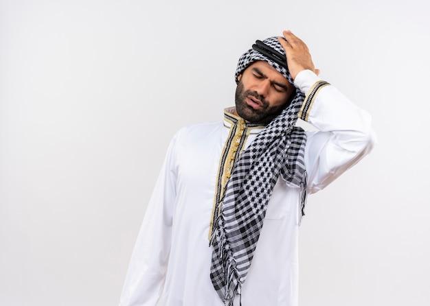 Uomo arabo in abbigliamento tradizionale che sembra confuso con la mano sulla testa per errore in piedi sul muro bianco