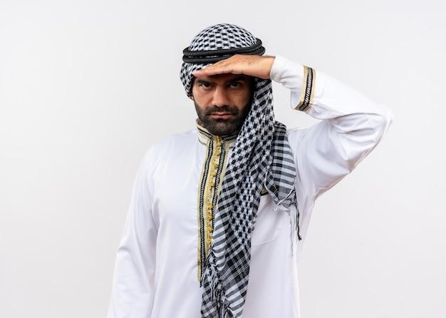 Uomo arabo in abbigliamento tradizionale che guarda lontano con la mano sulla testa in piedi sopra il muro bianco