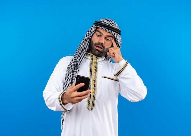 Arabic man in traditional wear looking at screen of his mobile confused standing over blue wall