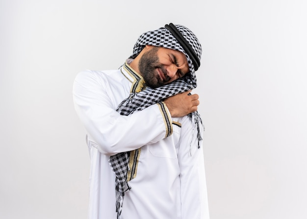 Arabic man in traditional wear looking unwell touching shoulder having pain standing over white wall