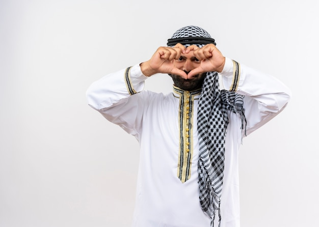 Arabic man in traditional wear making heart gesture with fingers looking through fingers smiling standing over white wall