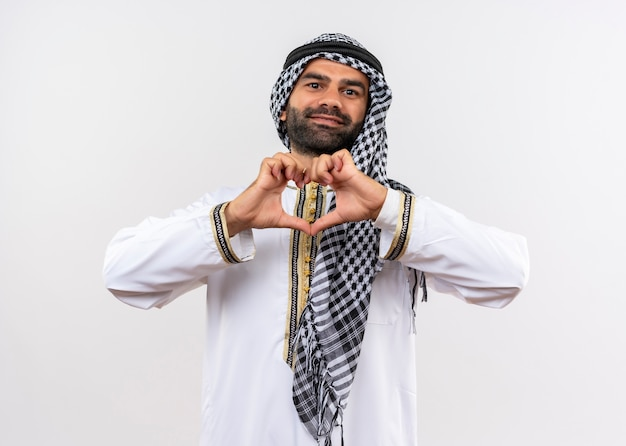 Arabic man in traditional wear making heart gesture with fingers smiling happy and positive standing over white wall