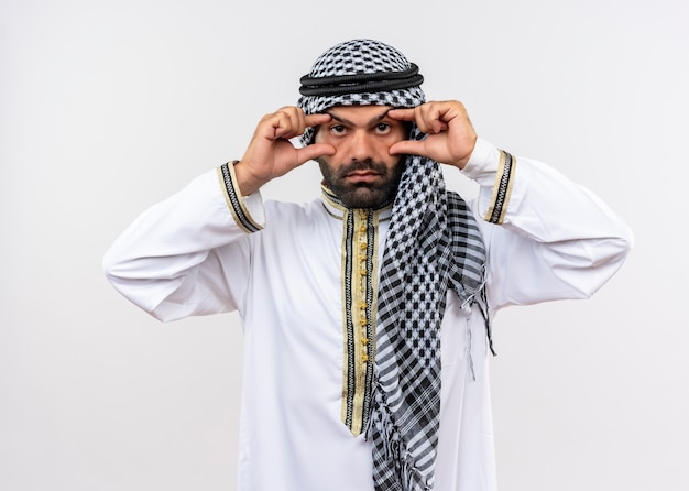 Arabic man in traditional wear opening eyes with fingers trying to see better standing over white wall