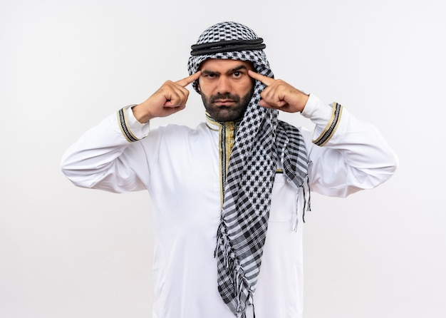 Arabic man in traditional wear pointing his temples with serious confident expression standing over white wall