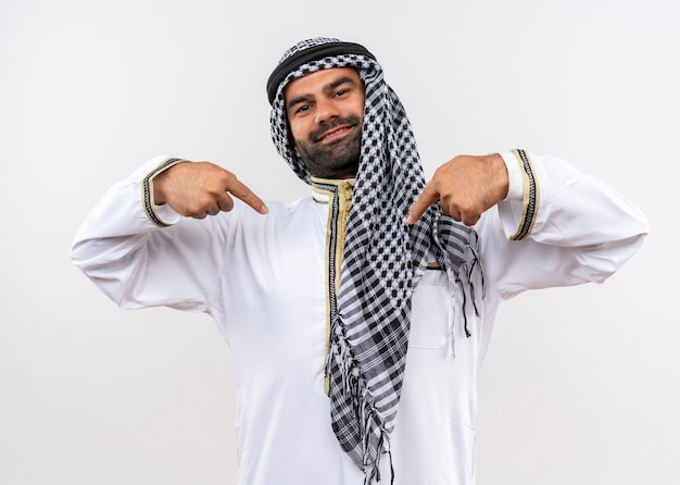Arabic man in traditional wear pointing with fingers to himself self-satisfied and proud standing over white wall