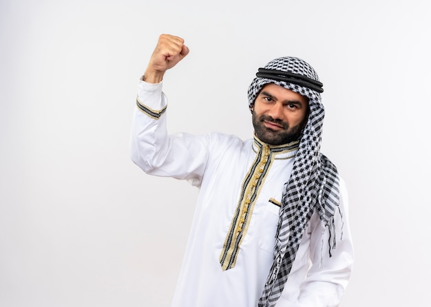 Arabic man in traditional wear raising fist smiling confident standing over white wall