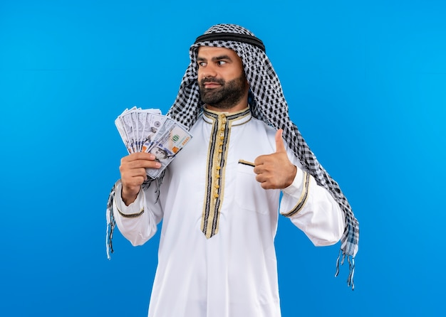 Arabic man in traditional wear showing cash looking aside smiling confident showing thumbs up standing over blue wall