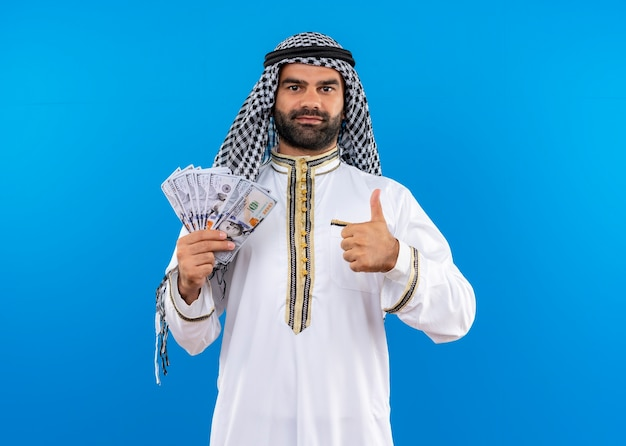 Arabic man in traditional wear showing cash smiling confident showing thumbs up standing over blue wall