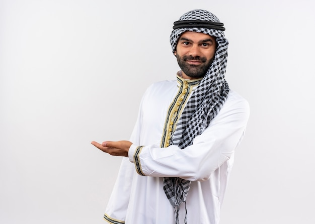 Arabic man in traditional wear smiling prsenting with arm of hand standing over white wall