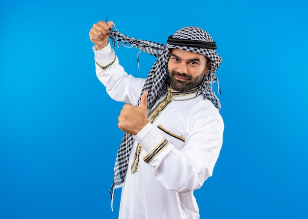 Arabic man in traditional wear smiling showing thumbs up standing over blue wall