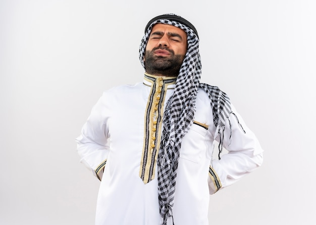 Uomo arabo in abbigliamento tradizionale che tocca la schiena guardando indisposto avendo dolore in piedi sopra il muro bianco