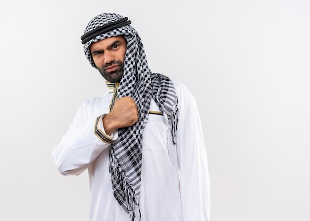 Arabic man in traditional wear with fist over his chest self-satisfied and confident standing over white wall