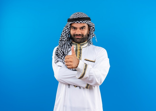 Arabic man in traditional wear  with smile on face showing thumbs up standing over blue wall