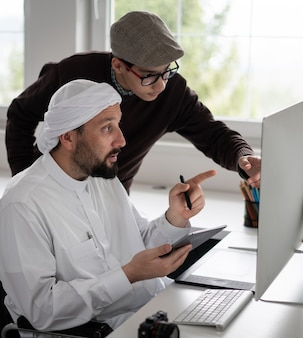 Arabic man in wheelchair at desk with computer
