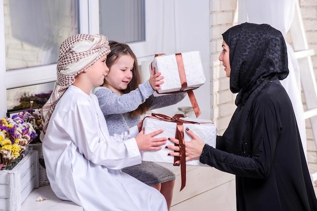 아랍어 어머니와 선물로 포즈를 취하는 아이들.실내.